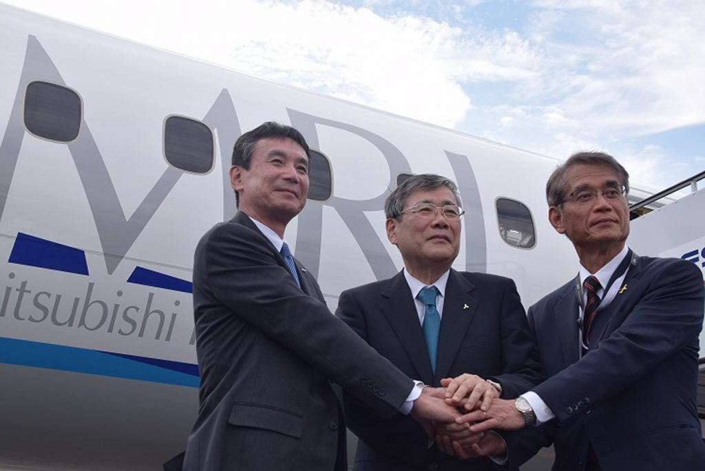 Mitsubishi Heavy Industries Ltd. President Shunichi Miyanaga (center), Mitsubishi Aircraft Corp. President Hisakazu Mizutani (right) and Yutaka Ito, a member of All Nippon Airways board of directors, shake hands following a flying display at the Farnborough International Airshow.