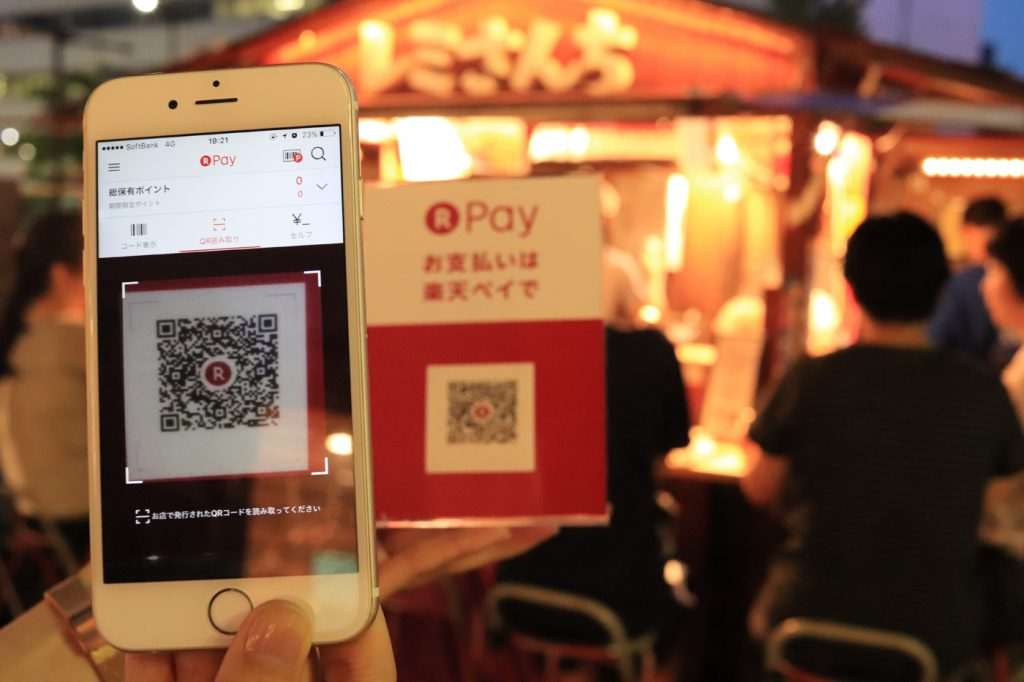 A customer reads the QR code at a food stall in the Fukuoka experiment.