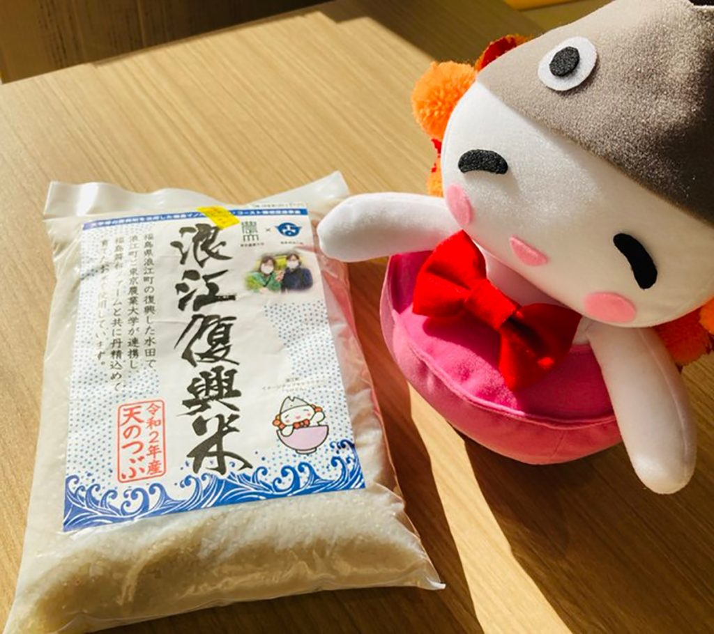 "Ukedon, the ""rice fairy"" mascot of Namie, Fukushima Prefecture, sits next to a bag of Namie Fukko Mai (Namie reconstruction rice) in a photo posted to the town's official Twitter account."