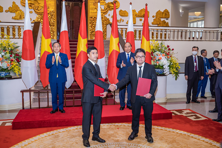 Bui Kien Cuong of Medring Co. (left) poses at a signing ceremony in Vietnam attended by the prime ministers of Japan and Vietnam in October 2020. | MEDRING CO.